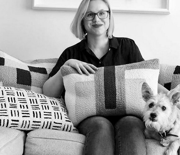 Black and white photo of young woman with cropped hair sittg on a couch with a striped pillow by a small terrier