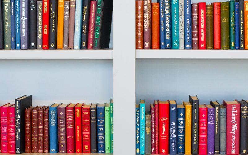 Multi colored books arranged neatly on a white bookshelf