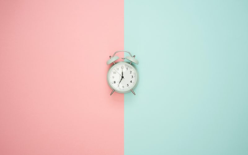 Antique alarm clock set behind a blush and aqumarine bakdrop.