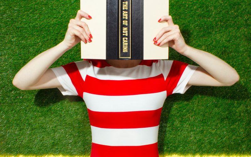 Women wearing red and white striped t-shirt using an open book to cover her face.