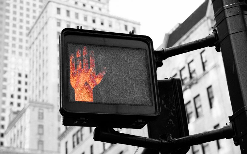 Red illuminated handprint indicating stop on a city street corner, black and white photo