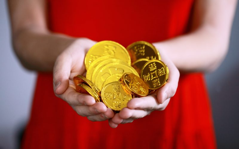 Woman in red dress holding a handful of bright gold coins