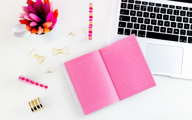 Bright pink notebook arranged near a stack of pink highlighers and sleek white laptop