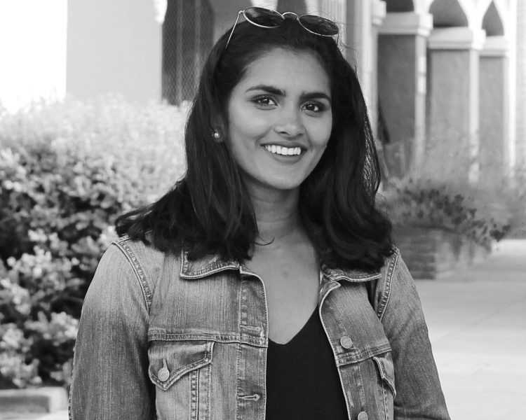 Young female entrepreneur wearing denim jacket smiling at camera