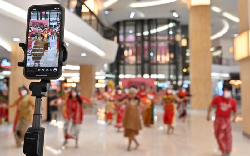 iPhone being held in a crowded mall ushering in a new era of fintech